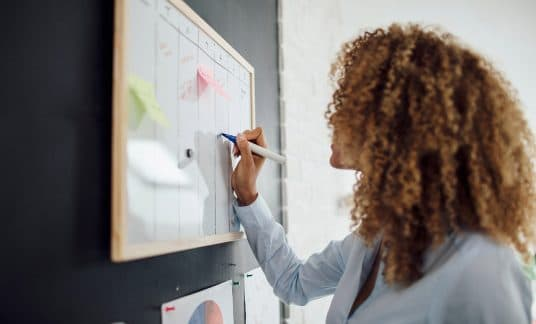 Woman making business schedule on a whiteboard.