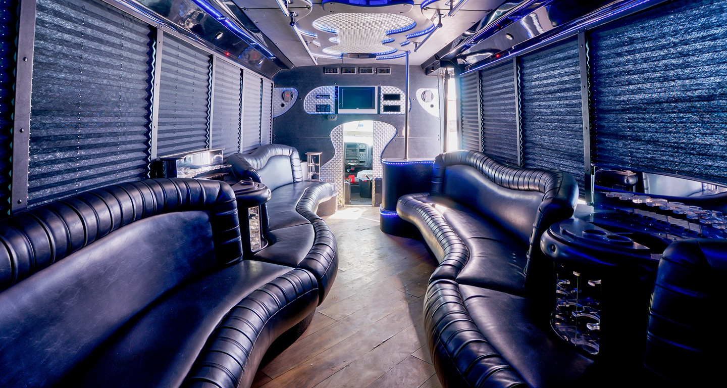 Interior of a shuttle, decorated with curvy leather couches and contemporary overhead lighting.