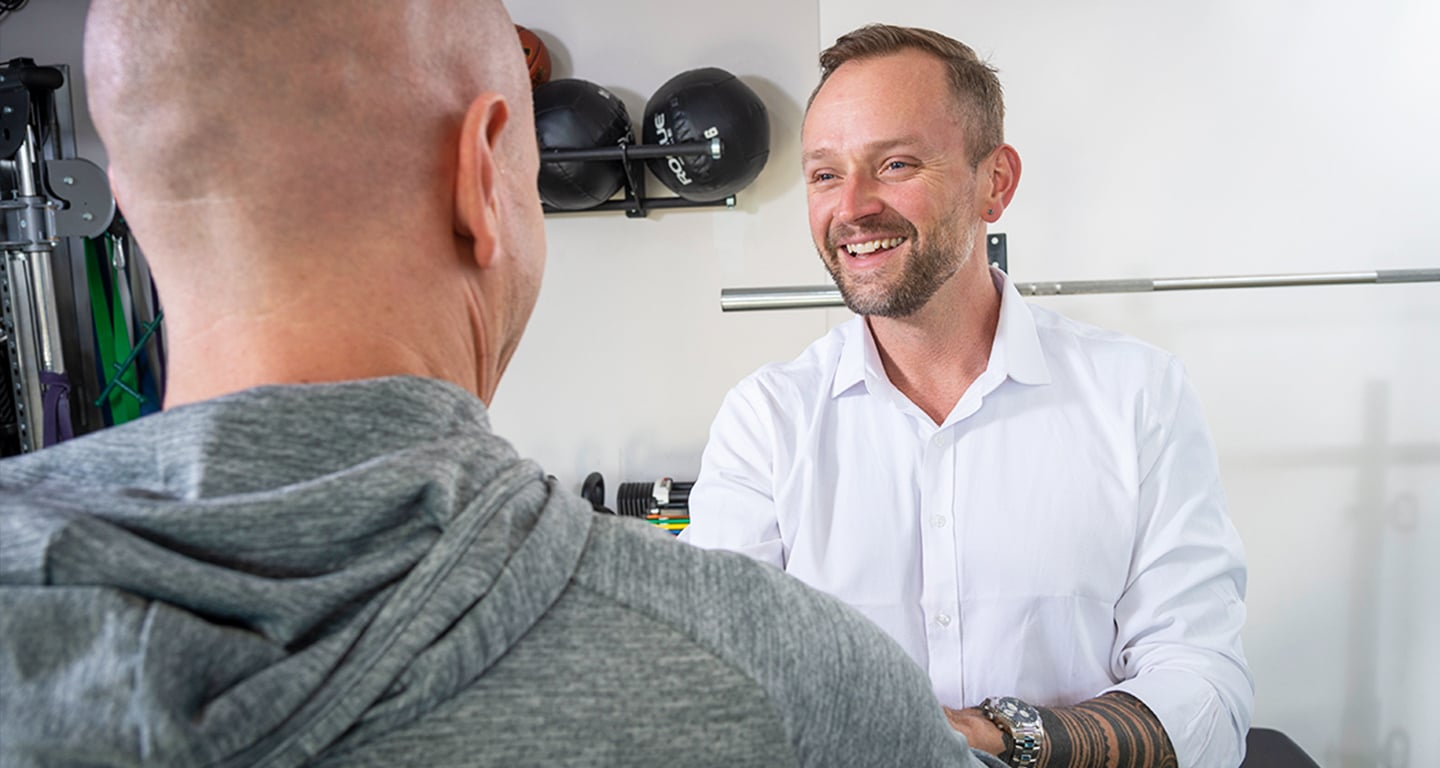 Symbio Physiotherapy director, Chris Woodard, shakes his client's hand.