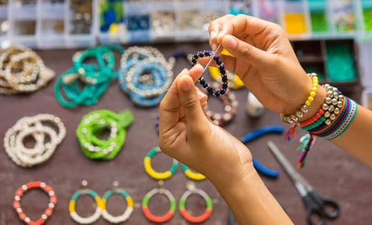 Woman creating a handmade bracelet to sell on an Etsy competitor site.