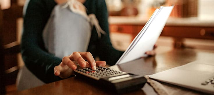 A woman uses a calculator as she refers to paperwork as she works with her invoicing software on her laptop.