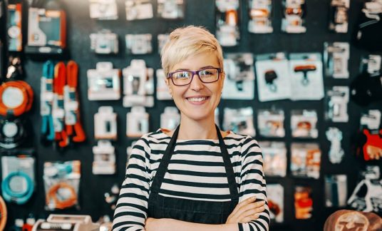 Smiling small business owner standing in a bicycle shop with arms crossed.