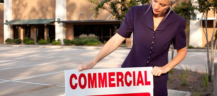 A real estate agent puts a sign in front of a commercial property.