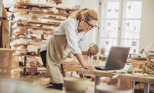 A business owner works on her website on her laptop. WooCommerce is a WordPress plug-in that can help you build your online business.
