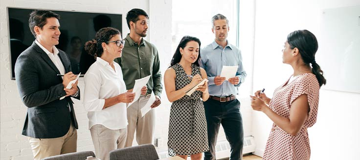 A group of new employees stand in a conference room and take notes while a female colleague speaks.