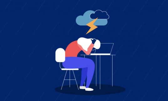 An unhappy worker sits at her desk. There is a storm cloud above her.