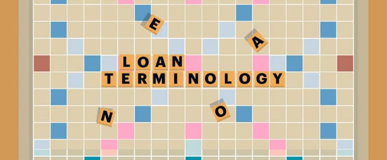 "Scrabble letters on a game board spell out ""Loan Terminology."""