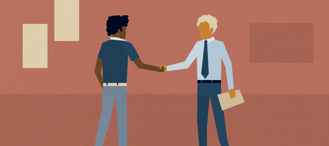 A new hire shakes hands with an employer in an office.
