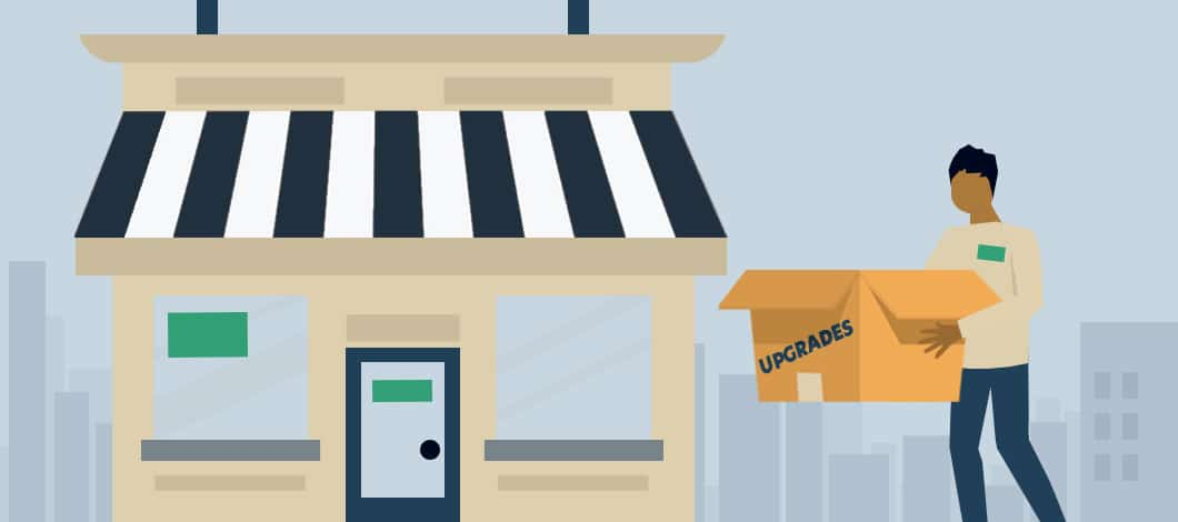 """A small business owner carries a box labeled """"Upgrades"""" into his small shop."""