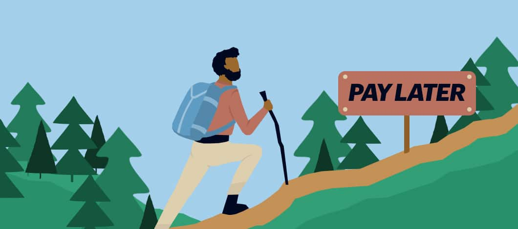 """A hiker with a walking stick comes across a """"Pay Later"""" direction sign on a trail heading up in the woods."""