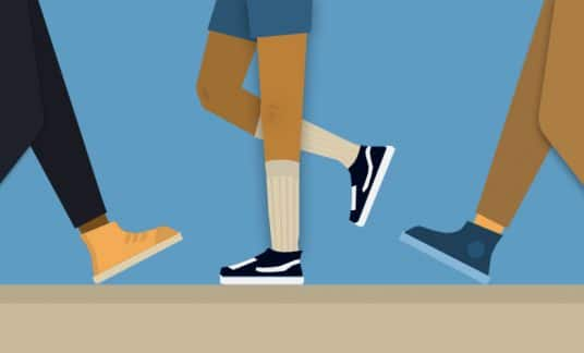 This is a close-up of feet of three people walking in different directions.