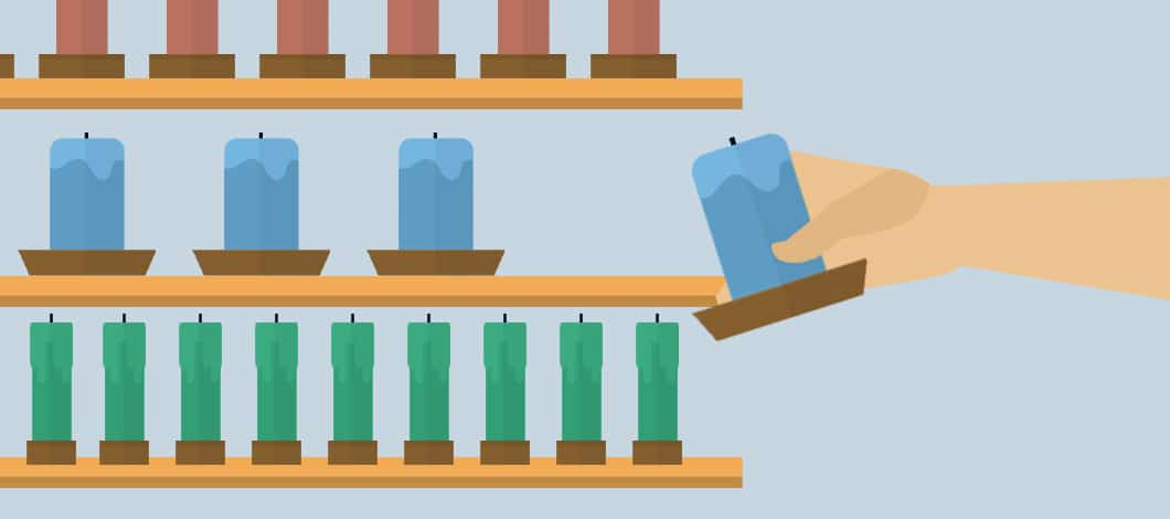 A hand places a blue candle on a store shelf that has other blue candles. The shelf above is filled with red candles and the shelf below has green candles.