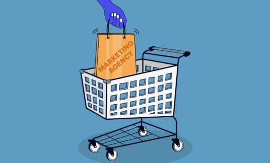 """A hand places a bag labeled """"Marketing Agency"""" into a shopping cart."""